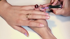 Manicure procedure woman putting purple polish on finger nail over white surface Stock Footage