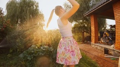 Young laughing woman dancing under water from garden hose at sunset Stock Footage
