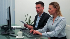 A man and a woman (both young and attractive) sit at a desk in an office, she Stock Footage
