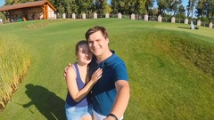 Footage from camera on selfie stick of happy young couple kissing at park Stock Footage