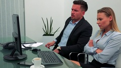 A man and a woman (both young and attractive) sit at a desk in an office, upset Stock Footage