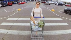 Young woman walking on parking lot at supermarket with full shopping cart Stock Footage