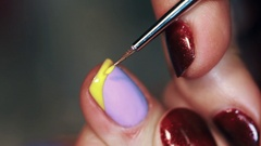 Manicure procedure woman hand paint yellow stripe on purple finger nail polish Stock Footage