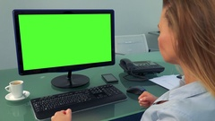 A young, beautiful woman sits in front of a computer with a green screen in an Stock Footage