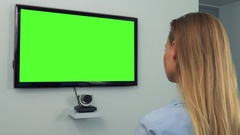 A woman (the back of her head to the camera) looks at a green television screen Stock Footage