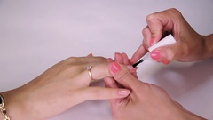 Woman manicurist painting nails polish transparent varnish in beauty saloon Stock Footage