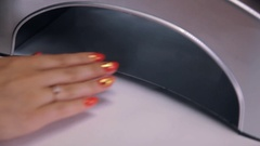 Female put fingers into uv purple manicure lamp to dry out nail polish Stock Footage