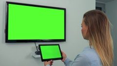 A woman looks in turns at a green television screen and a tablet with a green Stock Footage