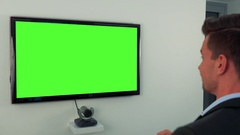 A man in a suit dances in front of a green television screen Stock Footage