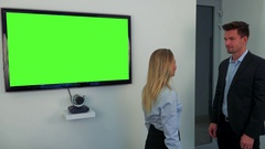 A man and a woman stand beside a green television screen and talk Stock Footage