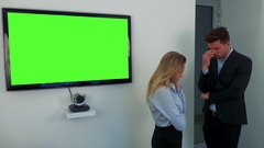 A man and a woman stand beside a green television screen, upset Stock Footage
