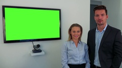 A man and a woman (both young and attractive) stand beside a green television Stock Footage