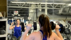 Athletic woman doing dumbbell push-press shoulder exercises in a mirror . Stock Footage