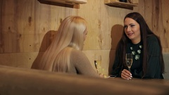 Two young women sitting in a cafe drinking champagne and talking. Stock Footage