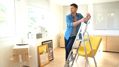 Couple in new home changing lamp bulb Stock Footage