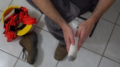 Man Massages Foot Workboot Off Overhead Stock Footage