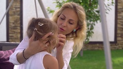 Mother with blond hair take care about little daughter Stock Footage