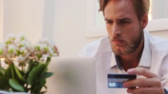 Good Looking Man With A Beard Shopping Online Using A Credit Card At Home Stock Footage