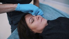 Plastic surgeon checking middle aged woman face before cosmetic surgery Stock Footage