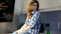 Worried girl wears ripped jeans and sits on worktop, steadycam shot Stock Footage