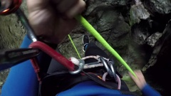 FPV: Man descending off steep and wet mountain wall into deep narrow gorge Stock Footage