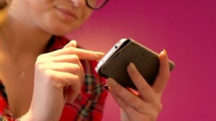 Girl in checked shirt browsing internet on smartphone, steadycam shot Stock Footage