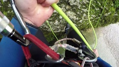 FPV: Man descending steep mossy mountain wall using rope, jumping into the river Stock Footage