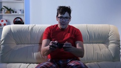 Bespectacled man playing video game while sitting on the couch Stock Footage