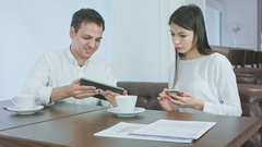 Smiling young man showing something on his tablet to female coworker holding Stock Footage
