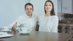 Cheerful business couple talking to the camera sitting in a cafe Stock Footage