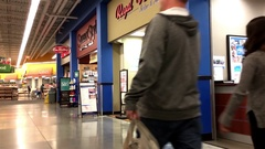 Pan shot of people buying auto insurance inside Walmart store Stock Footage