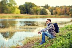 Man with backpack resting on river bank Stock Photos