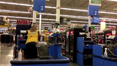 Pan shot of worker cleaning table at check out counter inside Walmart store Stock Footage