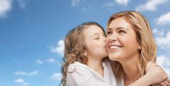 Happy little girl hugging and kissing her mother Stock Photos