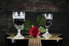 Red Rose and Wine Glasses Resting On Acoustic Guitar With Sign Happy Valent.. Stock Photos