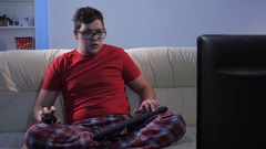Funny man playing a computer game sitting on big couch Stock Footage