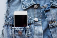 Smartphone in pocket of denim jacket or waistcoat Stock Photos