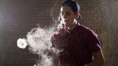 A teenage boy smokes an e-cigarette doing smoke circles Stock Footage