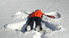 Young man throwing himself in the snow and making snow angels Stock Footage