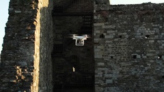 Slow motion video of a white quadcopter drone hovering in an ancient. Stock Footage