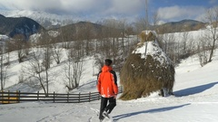 Man walking outside on a mountain at the countryside through the snow along.. Stock Footage