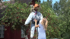 Villager girl stand scarecrow on cherry tree to protect berries. 4K Stock Footage