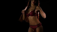 Long haired brunette in erotic red lingerie. Slow motion Stock Footage