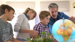 Teacher with kids in geography class looking at globe Stock Footage