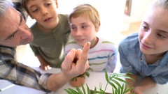 Teacher with kids in biology class learning about plants Stock Footage