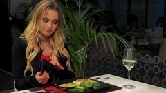 A young, beautiful woman sits at a table in a restaurant, holds a wallet and Stock Footage