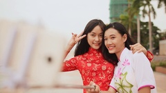 Two beautiful Vietnamese girl doing selfie with phone in national dresses Ao Dai Stock Footage