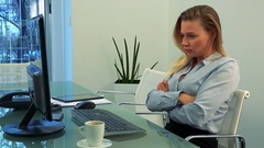 A young, beautiful woman works on a computer in an office and gets angry Stock Footage