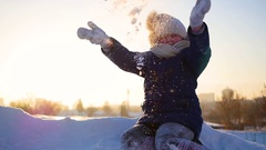 A girl throws snow above her head on sunset background Stock Footage