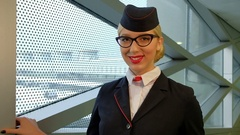 In airport stewardess with blond hair and glasses smiling affably Stock Footage